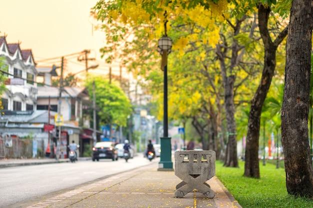 Marmurowa ławka w parku w mieście fosa do ruchliwej ulicy wieczoru w chiang mai