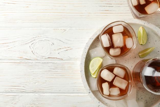 Marmurowa taca z szkłami whisky i wapno na białym tle, odgórny widok