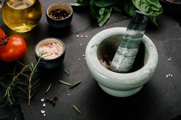 Marmurowa zaprawa do mielenia przypraw. rozmaryn, liście bazylii, sól morska, pomidory i oliwa z oliwek.