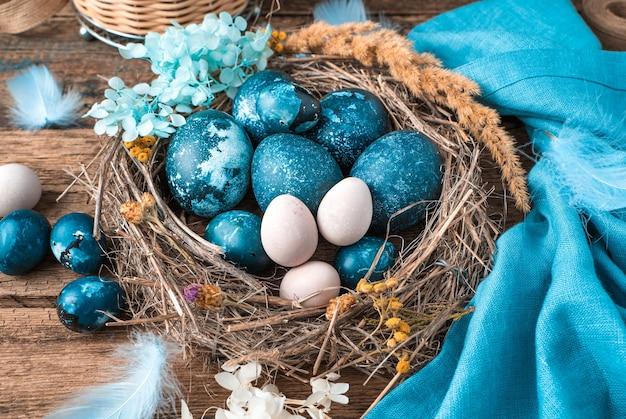 Marmurowo-niebieskie pisanki w wiklinowym gnieździe z piórami i kwiatami obok niebieskiej serwetki i