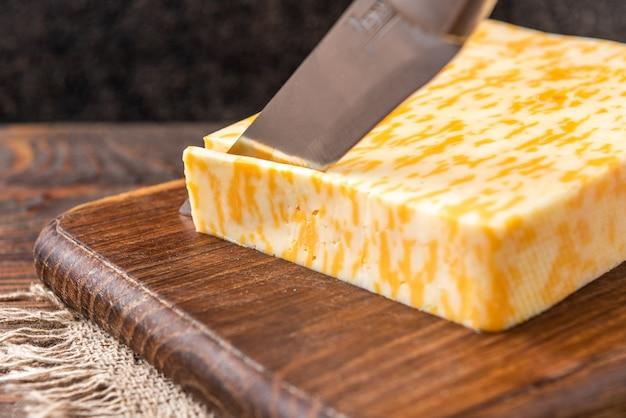Marmurowy ser na ciemnym drewnianym stole.
