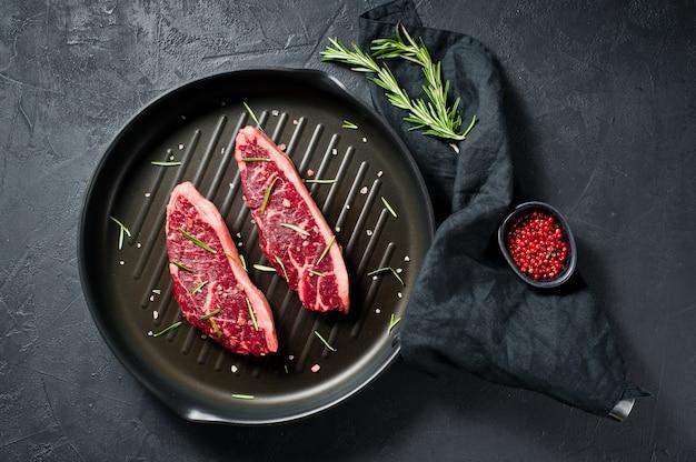 Marmurowy stek wołowy czarny angus na patelni grillowej.