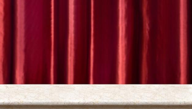 Marmurowy stół przy zamazanym żywym czerwonym luksusowym zasłony tłem.