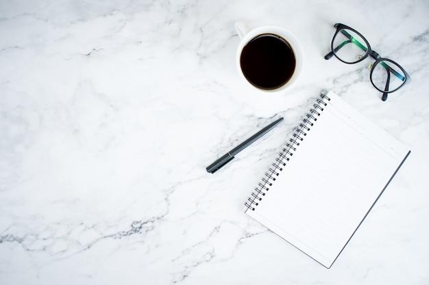 Marmurowy stół z notatnikiem, szklankami i kawą w widoku z góry