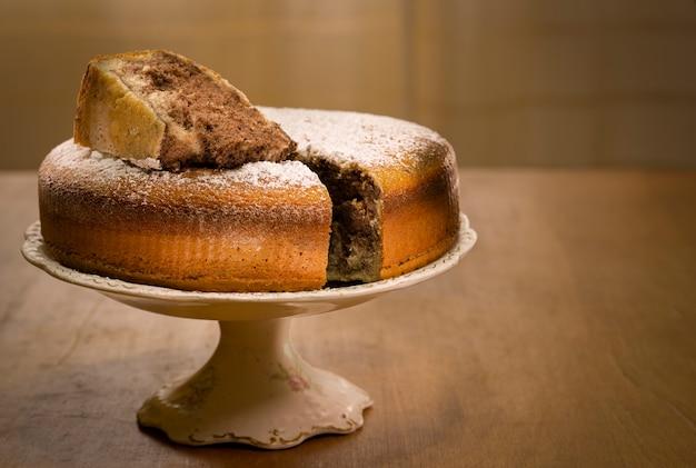 Marmurowy tort na starej podstawie i drewnianym stole z wyciętym kawałkiem