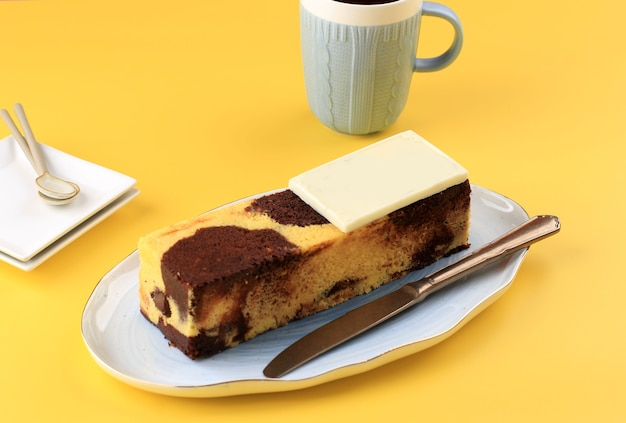 Marmurowy tort podróżny, mini bochenek marmurowy tort z roztopioną czekoladą w środku. znany również jako ciasto rurkowe. na białym talerzu