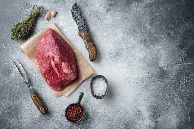 Marmurowy zestaw surowej wołowiny ze starym nożem tasakowym, na szarym stole, widok z góry na płasko