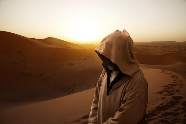 Marokańczyk spacerujący po wydmie na saharze