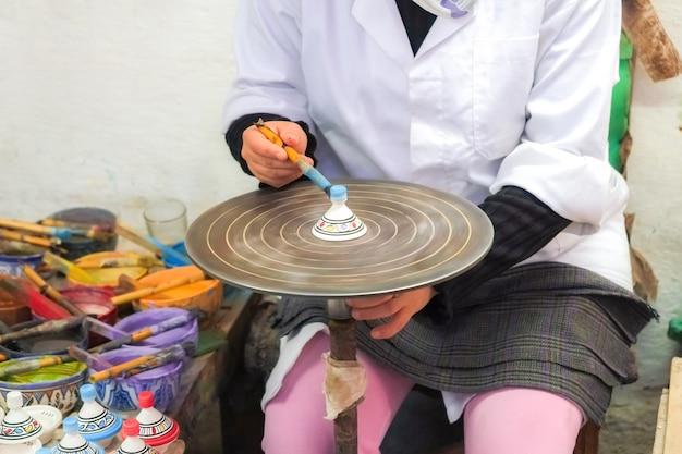 Marokańska kobieta maluje ceramiczną pamiątkę na obrotowym stole. medina of fez, morocco.