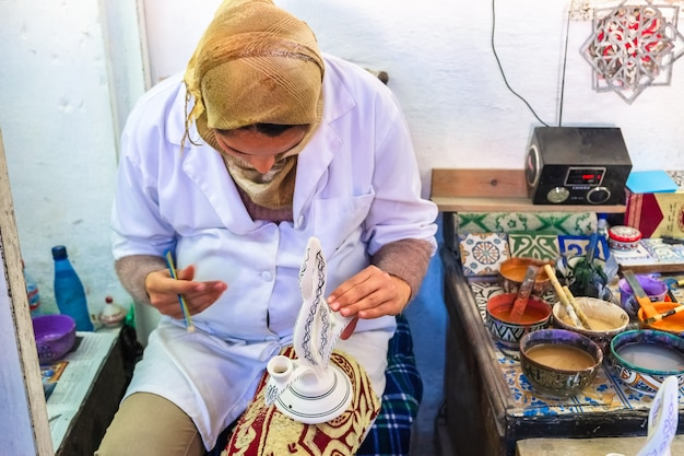 Marokańska kobieta maluje na ceramicznej garncarstwie. medina of fez, morocco.
