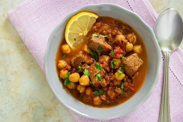 Marokańska zupa harira z mięsem, ciecierzycą, soczewicą, pomidorem i przyprawami. obfite, pachnące. przygotowanie do iftaru w świętym miesiącu ramadanu