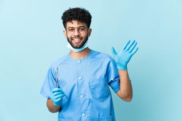 Marokański dentysta mężczyzna trzyma narzędzia na białym tle na niebieskiej ścianie pozdrawiając ręką z happy wypowiedzi