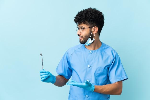 Marokański dentysta mężczyzna trzyma narzędzia na białym tle na niebiesko z wyrazem zaskoczenia, patrząc z boku