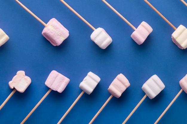 Marshmallows na drewnianych patyczkach, na niebieskim tle, makieta marshmallow