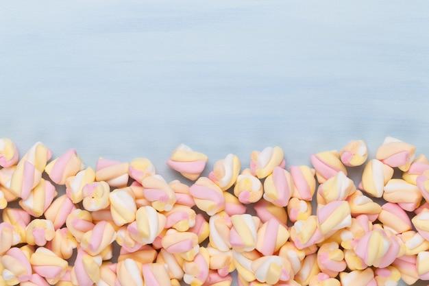 Marshmallows na niebieskim tle z copyspace. widok płaski lub górny. tło lub tekstura kolorowych mini marshmallows.