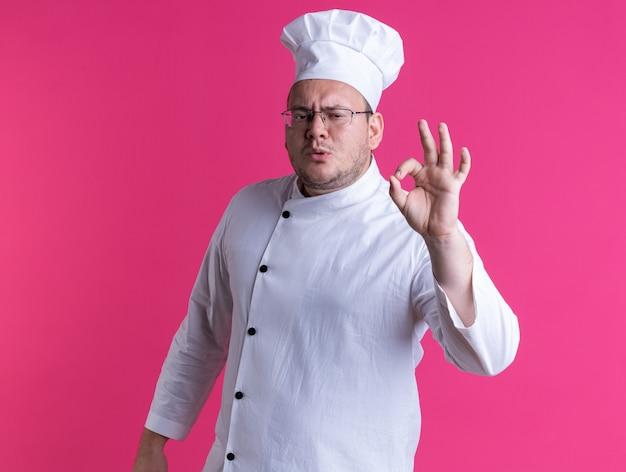 Marszcząc brwi dorosły mężczyzna kucharz ubrany w mundur szefa kuchni i okulary stojący w widoku z profilu, patrzący na przód, robiący ok znak na różowej ścianie