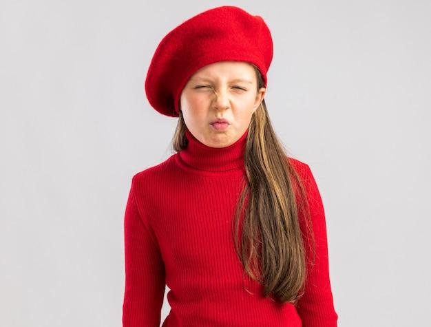 Marszcząc brwi mała blondynka ubrana w czerwony beret, patrząc na przód na białej ścianie z miejscem na kopię