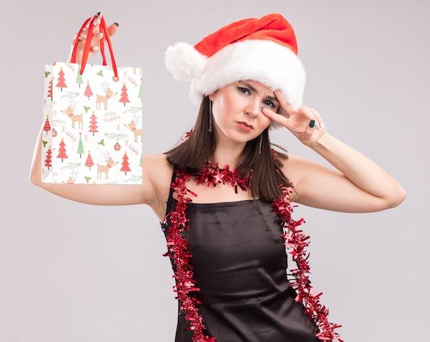 Marszcząc brwi, młoda ładna kaukaska dziewczyna nosi santa hat i blichtrową girlandę wokół szyi, trzymając świąteczną torbę prezentową, patrząc na kamerę pokazującą symbol znaku v w pobliżu oka na białym tle