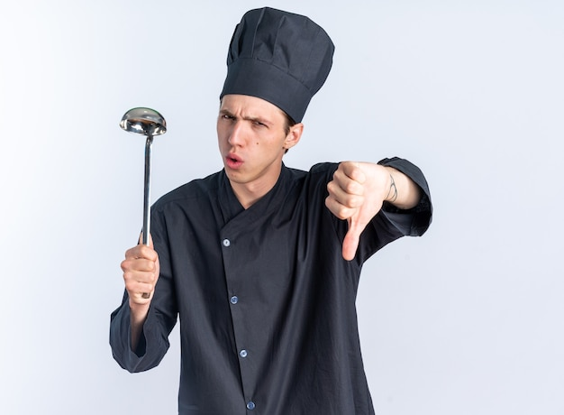 Marszcząc brwi młody blond kucharz w mundurze szefa kuchni i czapce trzymającej kadzi, patrząc na kamerę pokazującą kciuk w dół na białym tle na białej ścianie