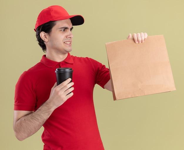 Marszcząc brwi młody kaukaski dostawca w czerwonym mundurze i czapce, trzymający papierową paczkę i plastikową filiżankę kawy, patrzący na paczkę