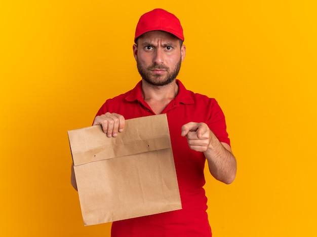 Marszcząc brwi młody kaukaski dostawca w czerwonym mundurze i czapce, trzymający papierowy pakiet, patrzący i wskazujący na kamerę