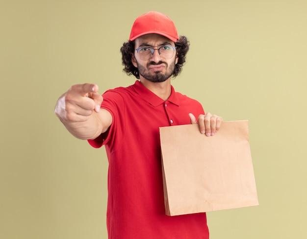 Marszcząc brwi młody kaukaski mężczyzna dostawy w czerwonym mundurze i czapce w okularach, trzymając papierowy pakiet patrząc i wskazując na oliwkowo-zielonej ścianie