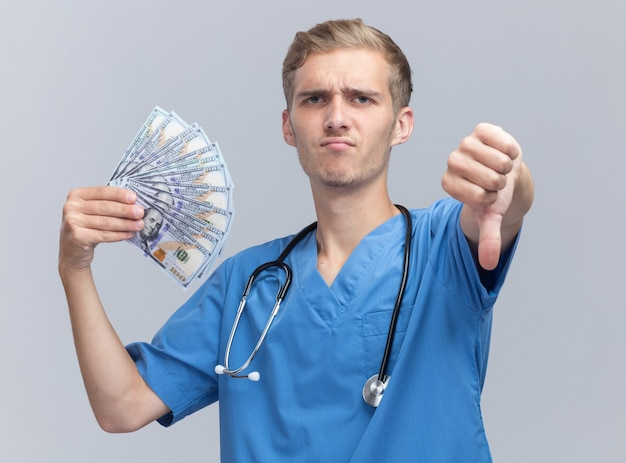 Marszcząc brwi, młody lekarz mężczyzna ubrany w mundur lekarza ze stetoskopem, trzymający gotówkę pokazujący kciuk w dół na białym tle na białej ścianie