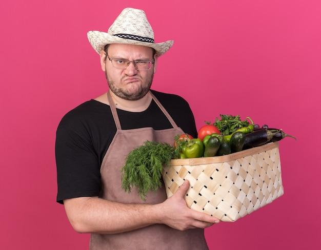 Marszcząc brwi młody mężczyzna ogrodnik w kapeluszu ogrodniczym, trzymający kosz warzyw na białym tle na różowej ścianie