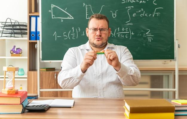 Marszcząc brwi młody nauczyciel w okularach siedzi przy biurku z przyborami szkolnymi w klasie trzyma kije liczące poziomo, próbując je złamać, patrząc na przód