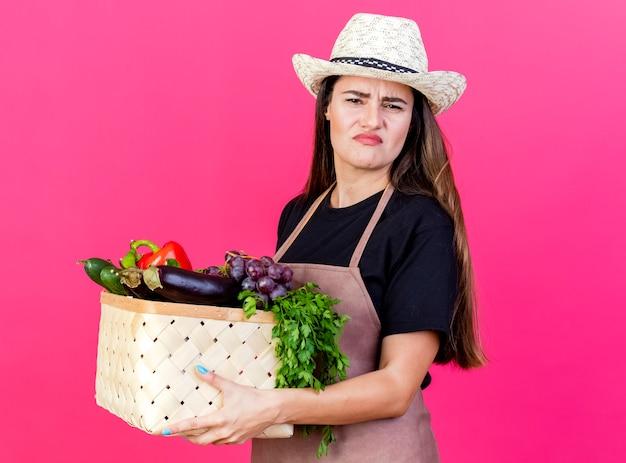 Marszcząc brwi piękna dziewczyna ogrodnik w mundurze na sobie kapelusz ogrodniczy trzymając kosz warzyw na różowo