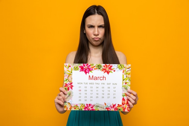 Marszcząc brwi piękna młoda dziewczyna na szczęśliwy dzień kobiety trzymająca kalendarz na pomarańczowej ścianie