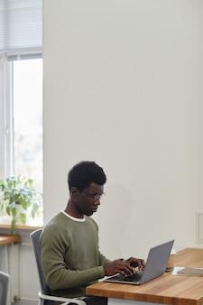 Marszcząc brwi, poważny młody biznesmen pracuje na laptopie przy biurku i odpowiada na e-maile klientów...
