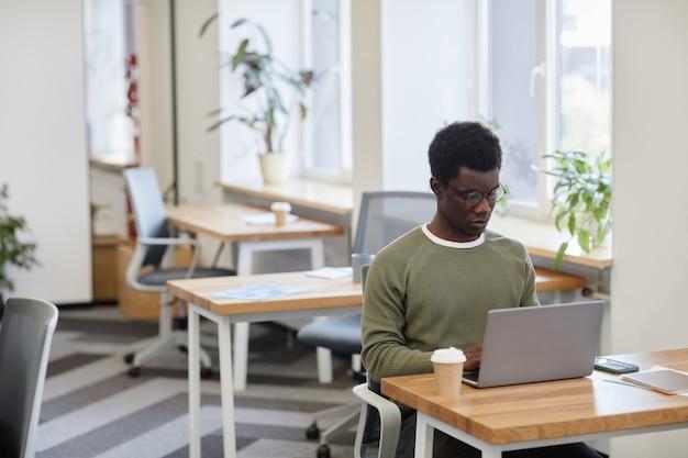 Marszcząc brwi, poważny programista pijący kawę i kodujący na laptopie w biurze typu open space