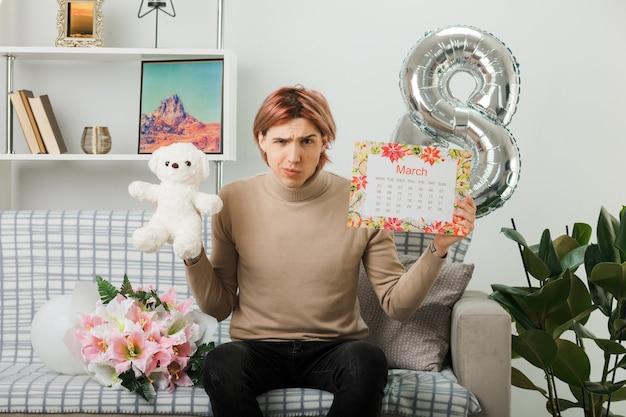 Marszcząc brwi, przystojny facet na szczęśliwy dzień kobiet, trzymający misia z kalendarzem, siedzący na kanapie w salonie