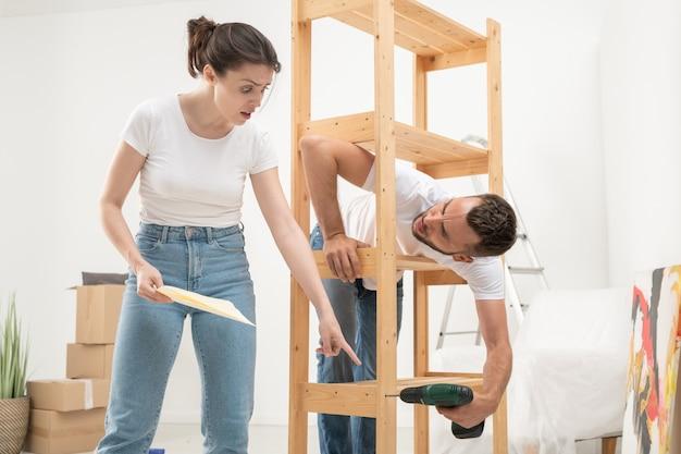 Marszcząc brwi, zdziwiona młoda kobieta patrząca z zakłopotaniem na plan montażu, podczas gdy jej zirytowany mąż montuje meble