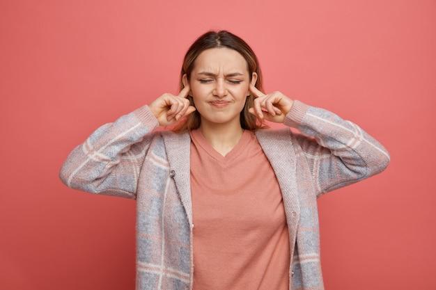 Marszcząca brwi dziewczyna wkłada palce do uszu z zamkniętymi oczami