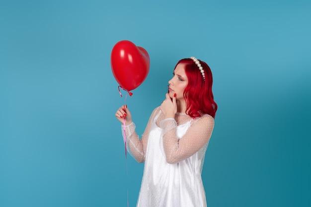 Marszcząca brwi kobieta w białej sukni z rudymi włosami patrzy na latający balon w kształcie serca