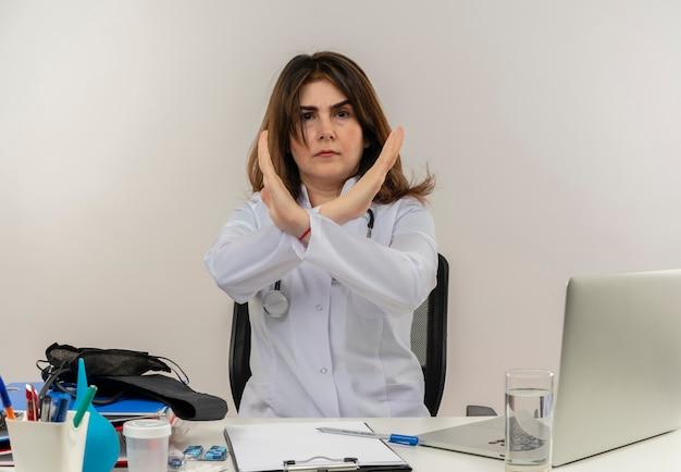 Marszcząca brwi kobieta w średnim wieku ubrana w szlafrok medyczny i stetoskop siedząca przy biurku ze schowkiem na narzędzia medyczne i laptopem nie wykonująca żadnego gestu izolowanego