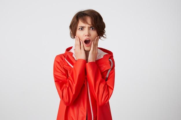Marszcząca brwi, krótkowłosa dziewczyna w białym golfie i czerwonym płaszczu przeciwdeszczowym, patrząc w kamerę z oburzeniem, z dłońmi na policzkach i szeroko otwartymi ustami, słyszy niewiarygodne wieści. stojąc na białym tle.