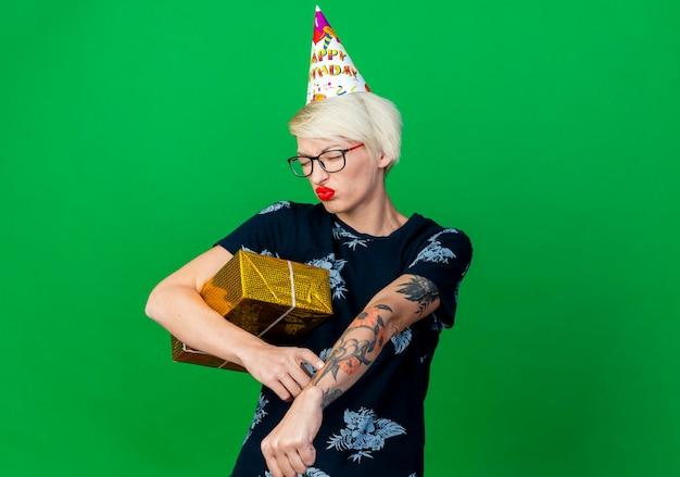 Marszcząca brwi, młoda blond kobieta w okularach i czapce urodzinowej trzymająca pudełko z prezentami robi gest spóźnienia z zamkniętymi oczami odizolowana na zielonej ścianie z miejscem na kopię