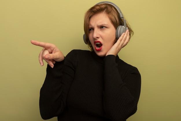 Marszcząca brwi młoda blondynka w słuchawkach, kładąca na nich dłoń, patrząca i wskazująca w bok