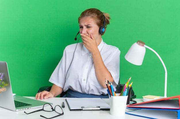 Marszcząca brwi młoda blondynka z call center w zestawie słuchawkowym, siedząca przy biurku z narzędziami do pracy, trzymająca rękę na ustach, patrząca na laptopa izolowanego na zielonej ścianie