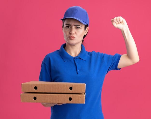 Marszcząca brwi młoda kobieta dostarczająca w mundurze i czapce trzymająca paczki pizzy, patrząca z przodu, wykonująca pukający gest z zaciśniętymi ustami odizolowanymi na różowej ścianie