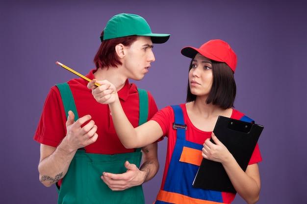 Marszcząca brwi młoda para w mundurze pracownika budowlanego i czapce dziewczyna trzyma ołówek i schowek patrząc i wskazując na bok z ołówkiem facet trzyma rękę w powietrzu patrząc na dziewczynę na białym tle