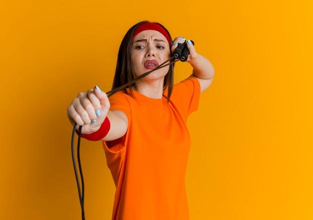 Marszcząca brwi, młoda sportowa kobieta nosząca opaskę i opaski na nadgarstkach ćwiczy ze skakanką, patrząc na nią na pomarańczowej ścianie z miejscem na kopię