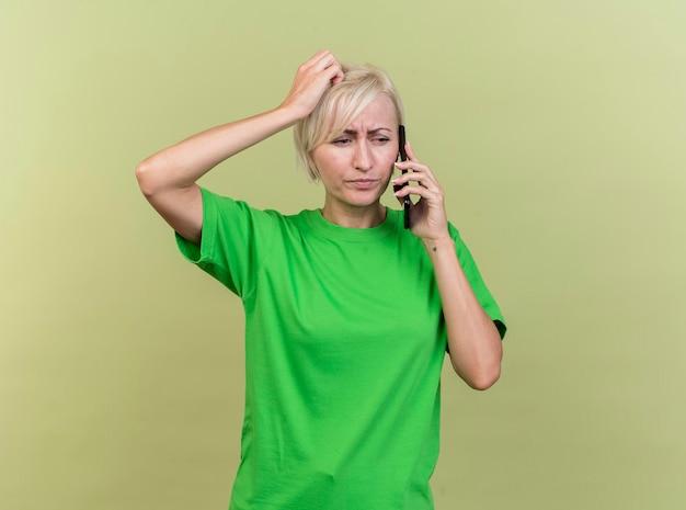 Marszcząca brwi w średnim wieku blond słowiańska kobieta rozmawia przez telefon, patrząc w bok, kładąc rękę na głowie odizolowaną na oliwkowej ścianie z miejscem na kopię