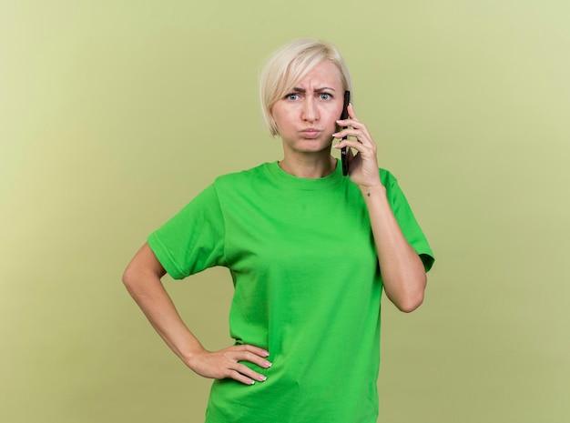 Marszcząca brwi w średnim wieku blond słowiańska kobieta rozmawia przez telefon, patrząc z przodu, trzymając ręce na talii odizolowane na oliwkowej ścianie z miejscem na kopię