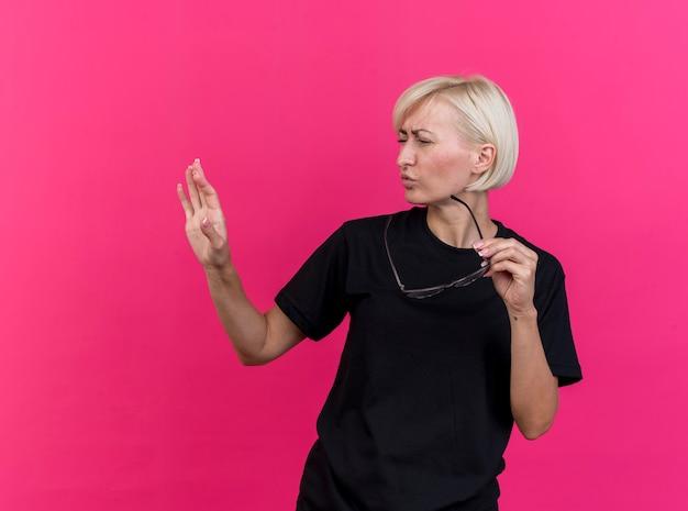 Marszcząca brwi w średnim wieku blond słowiańska kobieta trzyma okulary patrząc w bok, trzymając dłoń w powietrzu odizolowaną na szkarłatnej ścianie z miejscem na kopię