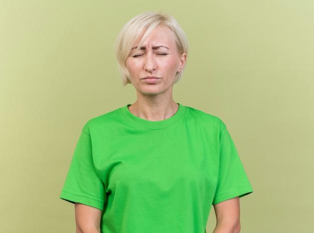 Marszcząca brwi w średnim wieku blondynka słowiańska kobieta stojąca z zamkniętymi oczami na białym tle na oliwkowym tle