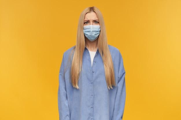 Marszcząca brwię dziewczyna, nieszczęśliwa kobieta o długich blond włosach. noszenie niebieskiej koszuli i medycznej maski na twarz. koncepcja ludzi i emocji. obserwując kamerę, odizolowane na pomarańczowym tle